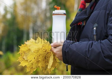 Man holding cup with drink and autumn leaves
