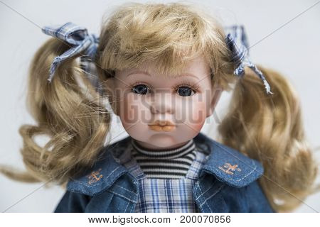Portrait of ceramic porcelain handmade vintage doll with wavy blond hair with tails in old blue plaid textile dress, denim jacket with embroidery, bow, striped sweater on white background.