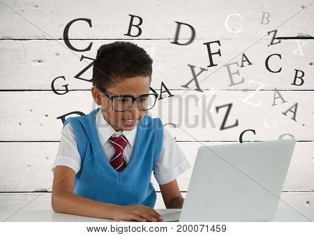 Digital composite of Many letters around Schoolboy on laptop with wood background