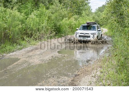 Overton, MO, USA - August 13, 2017:  Toyota 4Runner SUV (2016 Trail edition) carrying  a paddleboard  is driving through water puddles on a dirt road in Big Muddy National Fish and Wildlife Refuge.