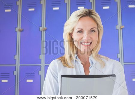 Digital composite of Mature female student holding file in front of lockers