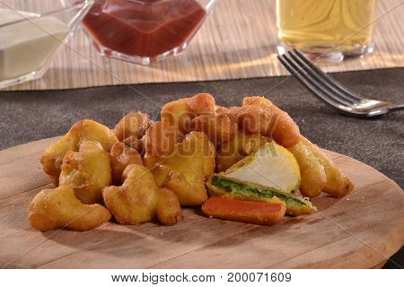 Fried breaded vegetables popper sticks and ketchup sauce.