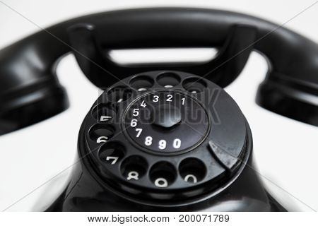 Old vintage stationary shiny black plastic telephone with round dial and a tube on the wire on white background