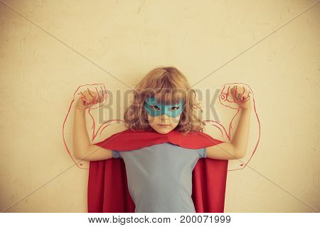 Strong superhero child with drawn muscles. Girl power and feminism concept