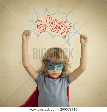 Superhero child against grunge wall background. Kid playing at home