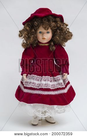 Portrait of ceramic porcelain handmade vintage doll with blue eyes, curly brown hair in old red velour dress with white and golden embroidery, big hat, shoes on white background.