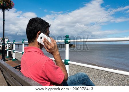 Middle aged Indian man sitting on a bench on the promenade near Penarth Pier overlooking the sea talking on his smartphone.