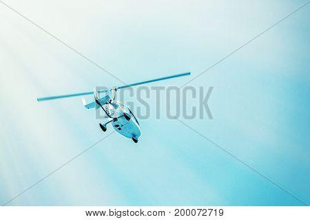 Small white gyroplane flying on blue sky Ultralight gyroplane