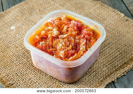 Frozen tomato sauce in a container on a wooden background