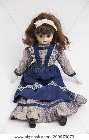 Portrait of ceramic porcelain handmade vintage doll with big eyes, wavy brown hair in old blue textile dress with embroidery, in shirt with gentle floral print , bow, black shoes on white background.