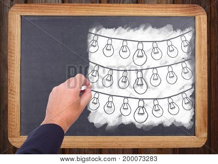 Digital composite of Hand drawing light bulbs on blackboard