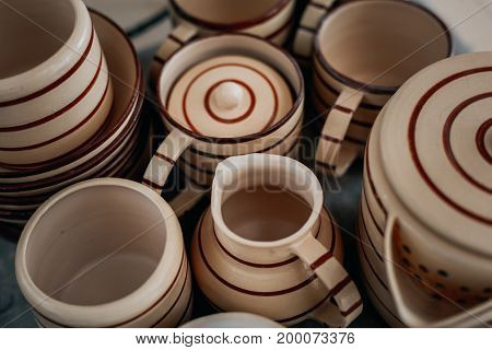 Handcrafted pottery set of dishes, handmade Utensils background, view from above, toned