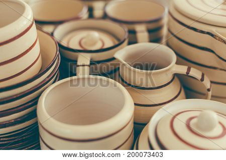 Handcrafted pottery set of dishes, handmade Utensils background, selective focus, toned