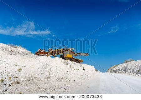 Yellow quarry heavy duty machine among white rocks in a mining quarry