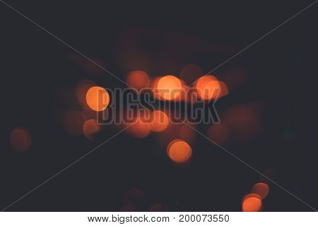 Abstract blurred dark background with round red orange bokeh circles, toned