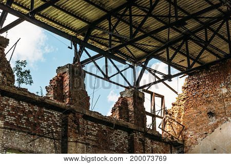 Ruined abandoned warehouse building interior, red brick wall construction
