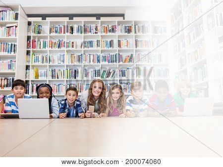 Digital composite of Elementary school teacher with class in library