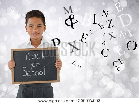 Digital composite of Many letters around Schoolboy holding back to school blackboard in front of bright bokeh background