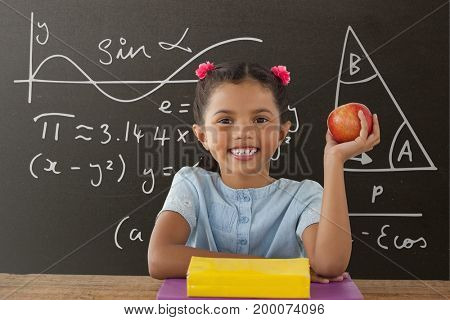 Digital composite of Happy student girl at table holding an apple against grey blackboard with education and school graph