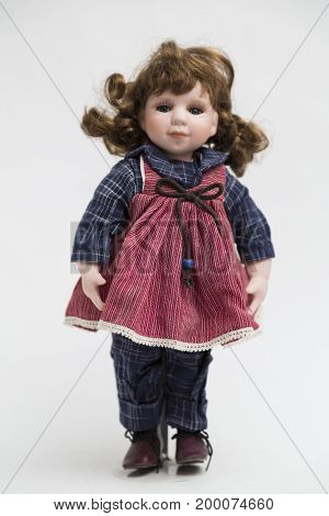 Portrait of ceramic porcelain handmade vintage smiling doll with ginger hair in old red textile sarafan dress with embroidery and bow of rope, in blue plaid shirt, red shoes on white background.