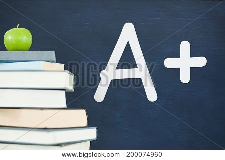 Digital composite of Books on the table against blue blackboard with A+ text