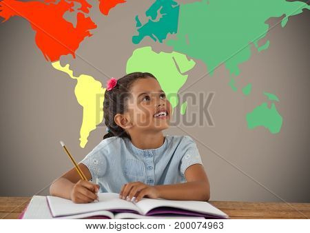 Digital composite of Schoolgirl writing at desk in front of colorful world map
