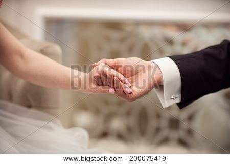 The groom holds the hand of the bride in his hand