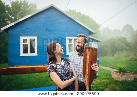 couple in love holding wooden paddles while standing opposite each other in courtyard