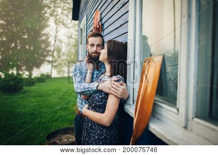 man hugging happy woman while standing with paddle near blue house wall