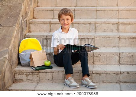The boy is a schoolboy sitting on the steps of the school and reading a book. Near a backpack and a package with breakfast and a green apple