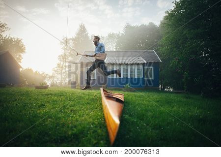 handsome man running with wooden paddle near canoe in courtyard