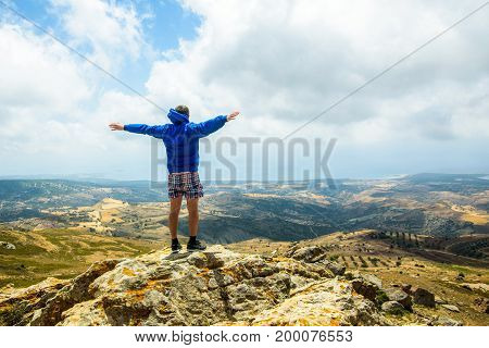 Happy man gesture of triumph with hands in the air on the mountain