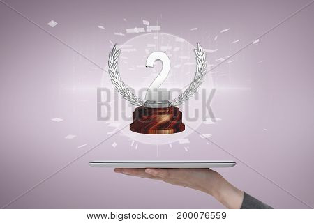 Digital composite of Person holding a tablet with a trophy