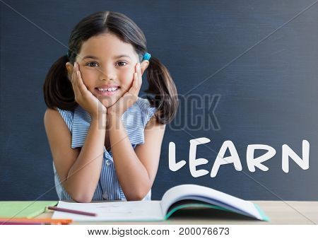 Digital composite of Student girl at table against blue blackboard with learn text