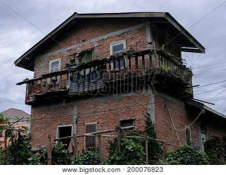 House made of red bricks with insecure balcony.