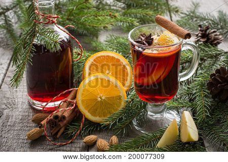 Christmas tradition drink. Hot Mulled wine with cinnamon and christmas tree on black slate dish. Close up , copy space.