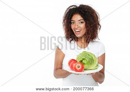 Image of happy young african woman standing isolated over white background. Holding vegetables.