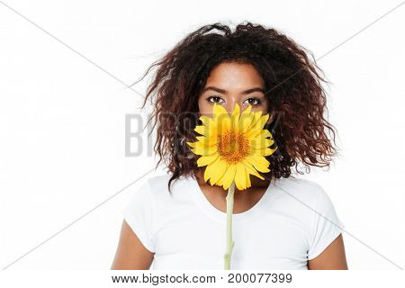 Image of cheerful young african woman standing isolated over white background. Looking camera holding flower.