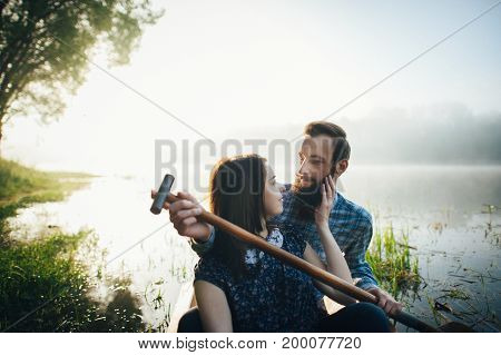 wife with husband sitting in canoe on coast of lake in sunny morning