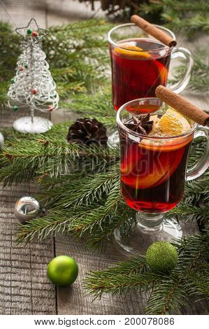 Christmas tradition drink. Hot Mulled wine with cinnamon and christmas tree on board. Close up, copy space.