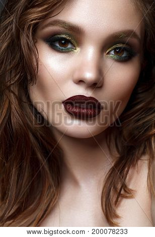 Beautiful young model with evening makeup and wavy hairstyle. Green smoky eyes and wine lips. trendy hairstyle