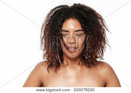 Image of happy young african woman standing isolated over white background clean her face with water.