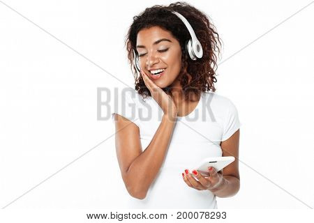 Image of happy young african lady standing isolated over white background. Looking aside listening music in headphones.