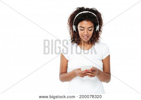 Image of happy young african lady standing isolated over white background. Looking aside listening music in headphones and chatting.