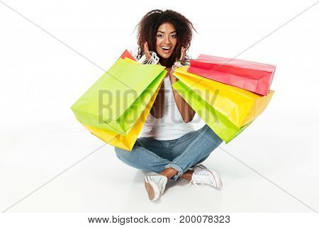 Picture of cheerful young african woman sitting isolated over white background. Looking camera holding shopping bags.