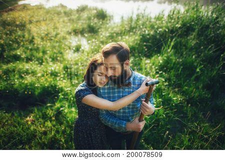 wife affectionately hugging husband on coast of lake in sunny morning