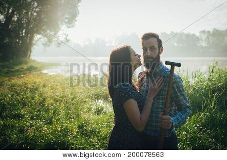 wife affectionately kissing husband on coast of lake in sunny morning