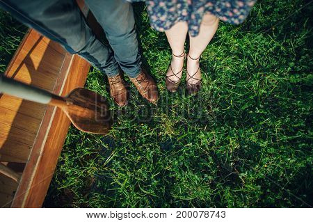 looking down view of two pairs of feet on green grass
