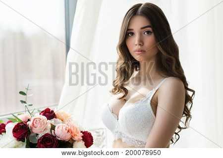 charming brunette in beautiful white bra in studio