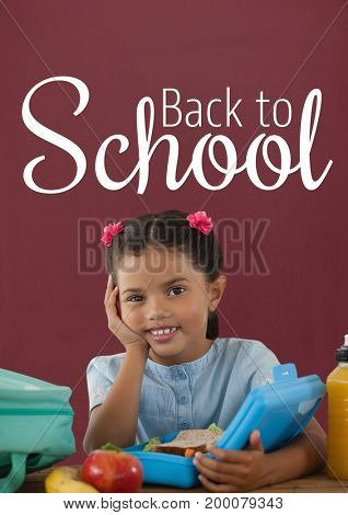 Digital composite of Happy student girl at table against red blackboard with back to school text